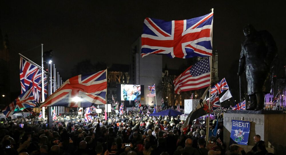 A Brexit supporter waves a US and Union flags as they wait for the festivities to begin in Parliament Square, the venue for the Leave Means Leave Brexit Celebration in central London on January 31, 2020, the day that the UK formally leaves the European Union