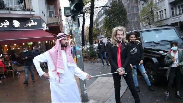 German YouTuber of Syrian origin, Fayez Kanfash, drags another person dressed as French President Emmanuel Macron through the streets of Berlin - Sputnik International