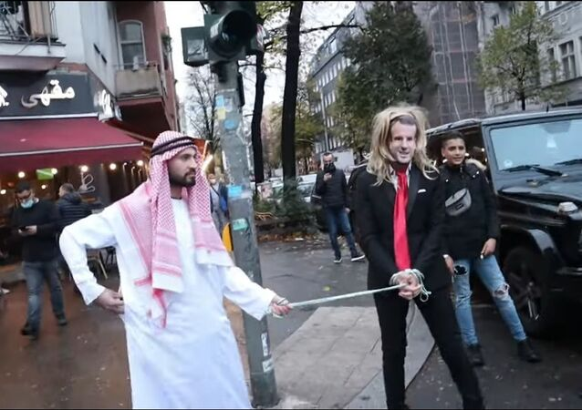 German YouTuber of Syrian origin, Fayez Kanfash, drags another person dressed as French President Emmanuel Macron through the streets of Berlin