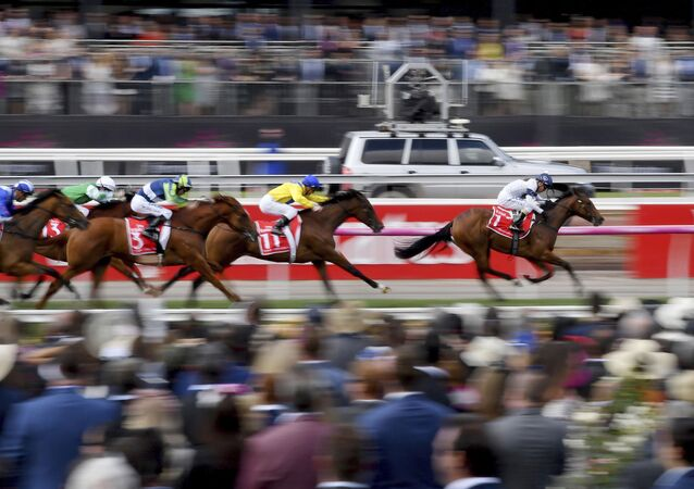 In this Nov. 7, 2017, file photo, horse race past the crowd during race 1 before the running of the Melbourne Cup at Flemington Racecourse in Melbourne. In Australia, where horse racing is arguably more popular than in any other country on the planet, the sport is continuing, minus the spectators, despite the nation's struggle to contain the new coronavirus.