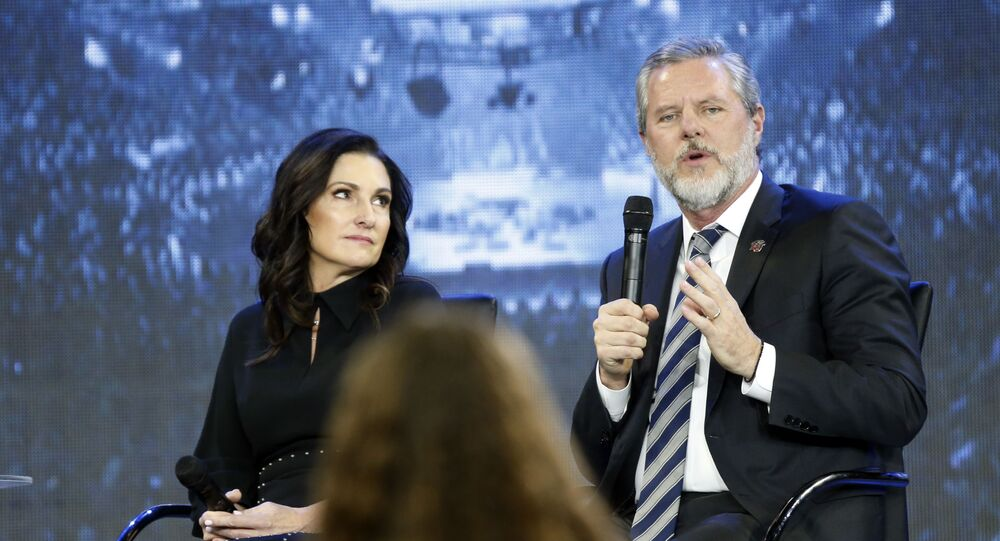 In this Wednesday, Nov. 28, 2018 file photo, Jerry Falwell Jr., right, answers a student's question, accompanied by his wife, Becki, during a town hall meeting on the opioid crisis at a convocation at Liberty University in Lynchburg, Va. On Aug. 7, 2020, Falwell stepped down, at least temporarily, from his role as the president of the school.