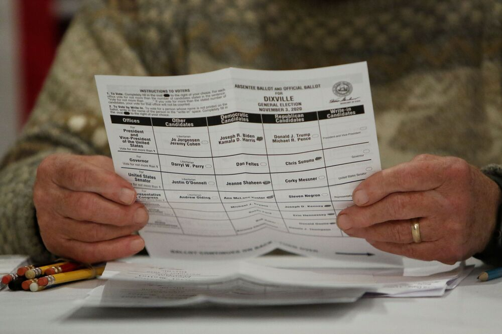 Town moderator Tom Tillotson holds a ballot shortly after midnight for the US presidential election at Hale House at the Balsams Resort in the hamlet of Dixville Notch, New Hampshire, US, 3 November 2020.