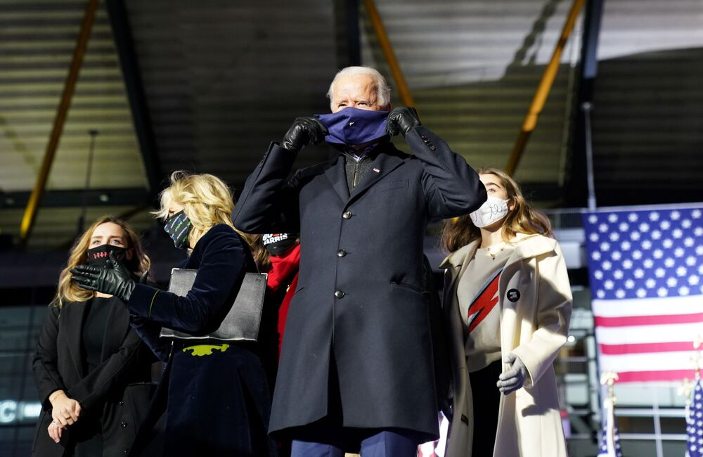 US presidential nominee for the Democrats and former Vice-President Joe Biden puts on a face mask while standing on stage with his family during a drive-in campaign rally at Heinz Field in Pittsburgh, Pennsylvania, US, 2 November 2020.
