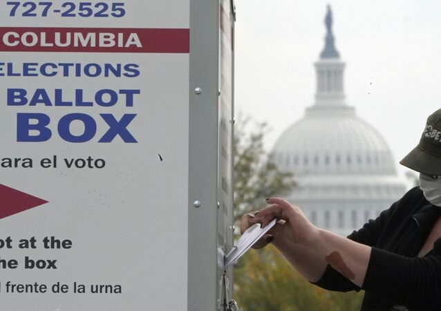 With the dome of the US Capitol visible, a voter drops a ballot into an early voting drop box, Wednesday, 28 October 2020, at Union Market in Washington.