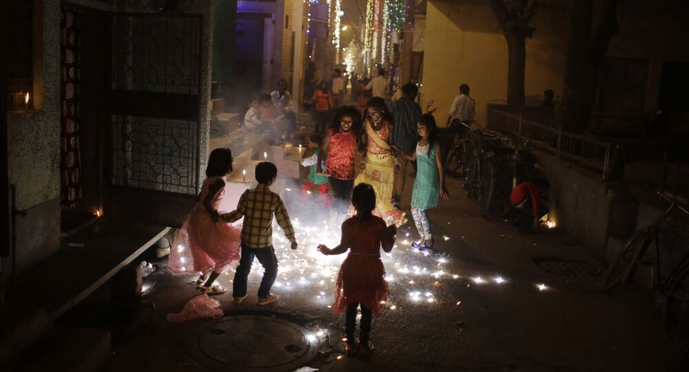 In this Wednesday, Nov. 11, 2015 photo, children burn fire crackers outside their houses in New Delhi, India