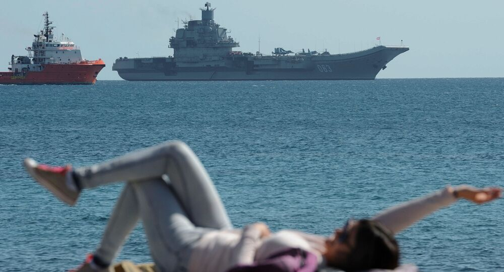 A woman enjoy the sea and the sun as in the background see the Russian aircraft carrier Admiral Kuznetsov lies at anchor off Cyprus' largest port of Limassol on Thursday, Feb. 27, 2014