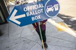 An election worker directs voters to a ballot drop off location on November 2, 2020 in Portland, Oregon. Oregons voting system allows for ballot processing before the start of Election Day.