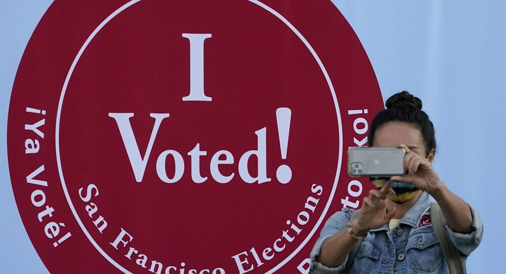 A woman takes a photo in front of an I Voted sign at a San Francisco Department of Elections voting center in San Francisco, Monday, Nov. 2, 2020, ahead of Election Day.