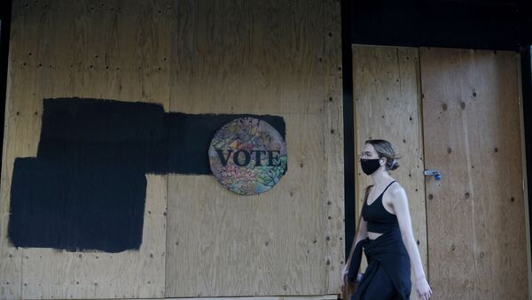 A woman walks past a Vote sign on wooden boards covering the exterior of Chloe Gallery in San Francisco, Monday, Nov. 2, 2020, ahead of Election Day.  - Sputnik International