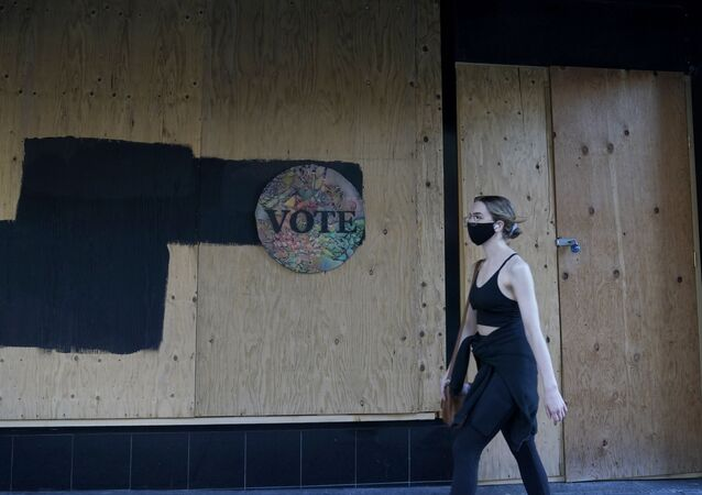 A woman walks past a Vote sign on wooden boards covering the exterior of Chloe Gallery in San Francisco, Monday, Nov. 2, 2020, ahead of Election Day.