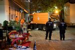 Hastily left drinks are seen on a table as cleaning crews and police work outside a restaurant near the scene of an attack in Vienna, Austria on November 3, 2020, one day after a shooting at multiple locations across central Vienna.
