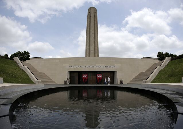 In this photo taken Wednesday, May 21, 2014, visitors walk along a reflecting pool outside the main entrance to the National World War I Museum at Liberty Memorial in Kansas City, Mo. The museum focuses on the century-old Great War.