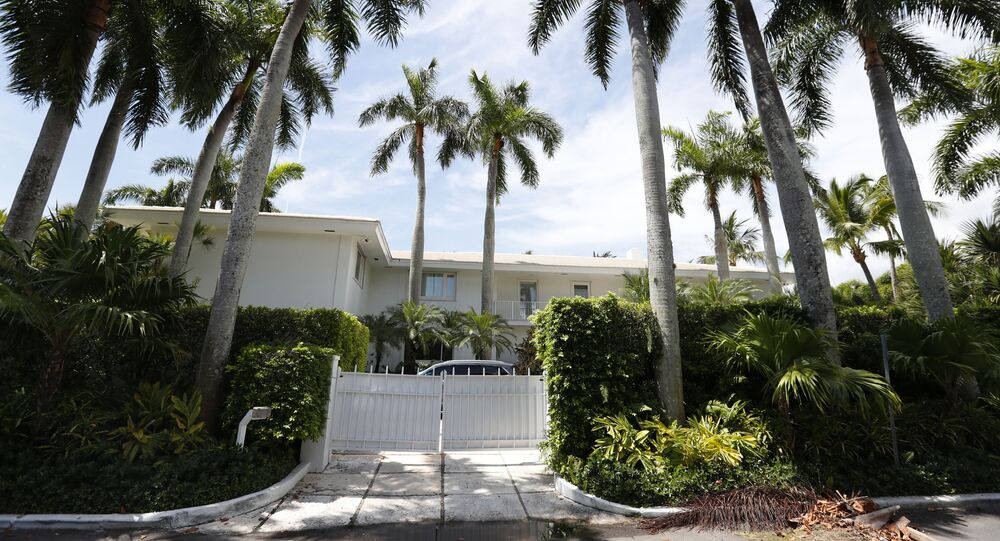 FILE - In this July 10, 2019 file photo, palm trees shade the Florida residence of Jeffrey Epstein in Palm Beach, Fla. The FBI said Thursday July 2, 2020, Ghislaine Maxwell, a British socialite who was accused by many women of helping procure underage sex partners for Epstein, has been arrested in New Hampshire. The court papers said Epstein's abuse of girls occurred at his Manhattan mansion and other residences in Palm Beach, Florida; Sante Fe, New Mexico and London. (AP Photo/Wilfredo Lee, File)