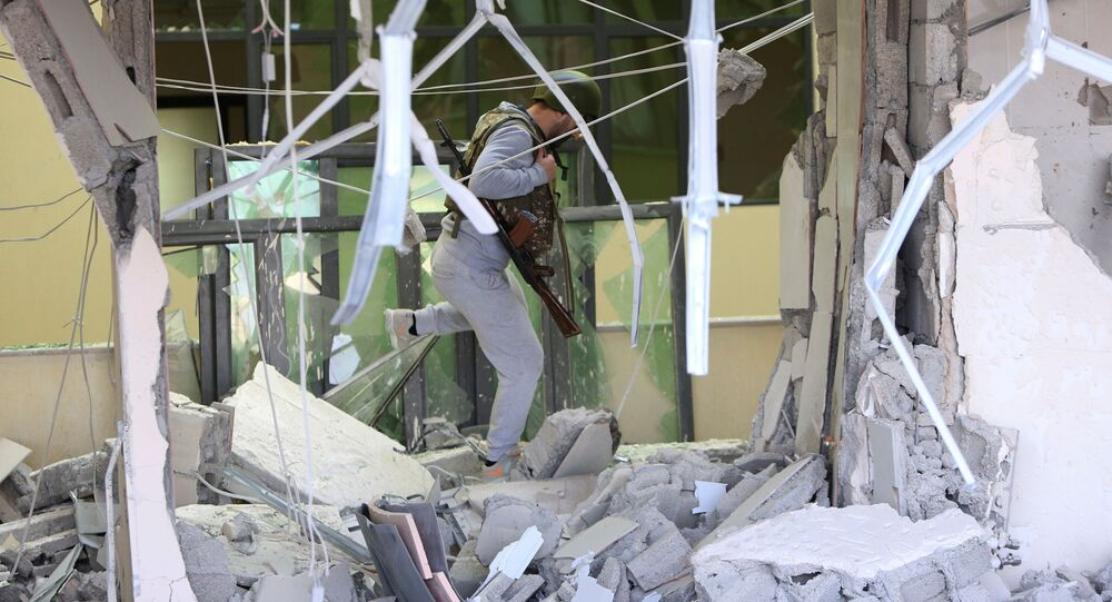 An armed man walks inside a damaged medical centre following recent shelling in Stepanakert, in the course of a military conflict over the breakaway region of Nagorno-Karabakh, October 28, 2020.