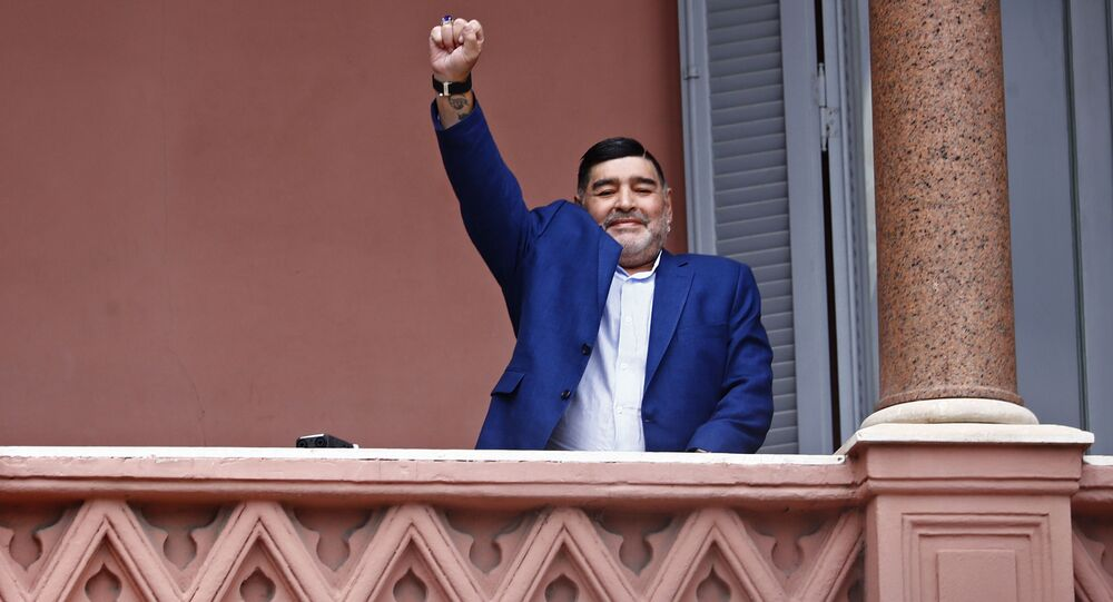 Former soccer great Diego Maradona acknowledges fans below at the Casa Rosada government house after his meeting with Argentine President Alberto Fernandez in Buenos Aires, Argentina, Thursday, Dec. 26, 2019.