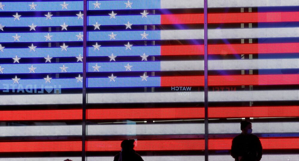 People stand next to a screen displaying a U.S. flag in Times Square during the 2020 U.S. presidential election in New York City, New York, U.S. November 4, 2020.