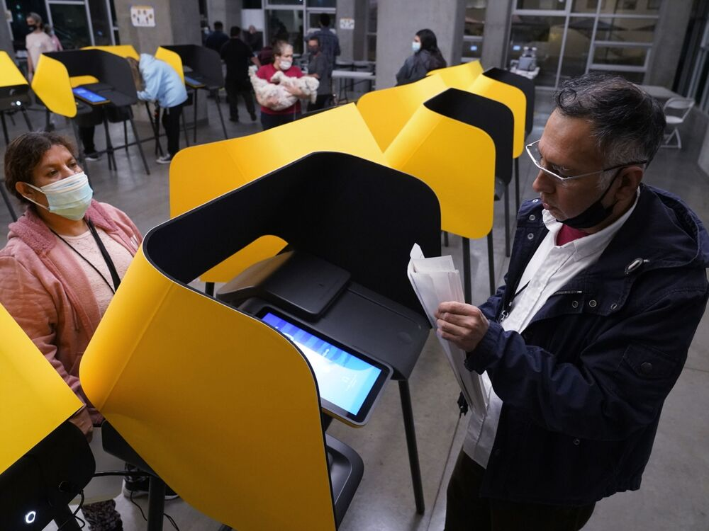 Fernando Dejo, right, and Sabina Vasquez retrieve paper votes from ballot-marking devices, or vote recorders, as a polling station closes in Los Angeles on Tuesday, 3 November 2020.