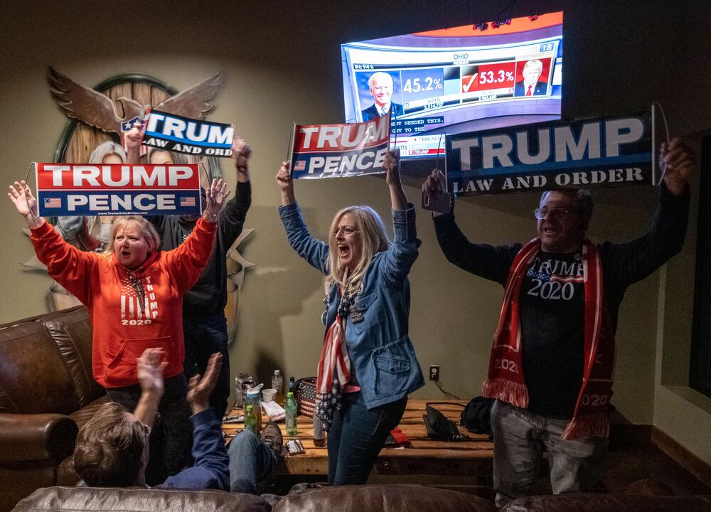 Supporters of the US President celebrate as they watch Ohio being called for Donald Trump at a Republican watch party at Huron Valley Guns in New Hudson, Michigan, 3 November 2020.
