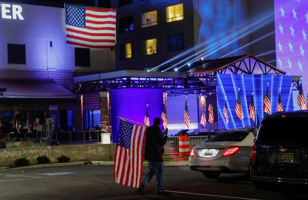 A Biden supporter carries an American flag across the parking lot where US presidential nominee for the Democrats, Joe Biden, will hold his 2020 US presidential election night event as a drive-in rally because of coronavirus restrictions, in Wilmington, Delaware, US, 3 November 2020.