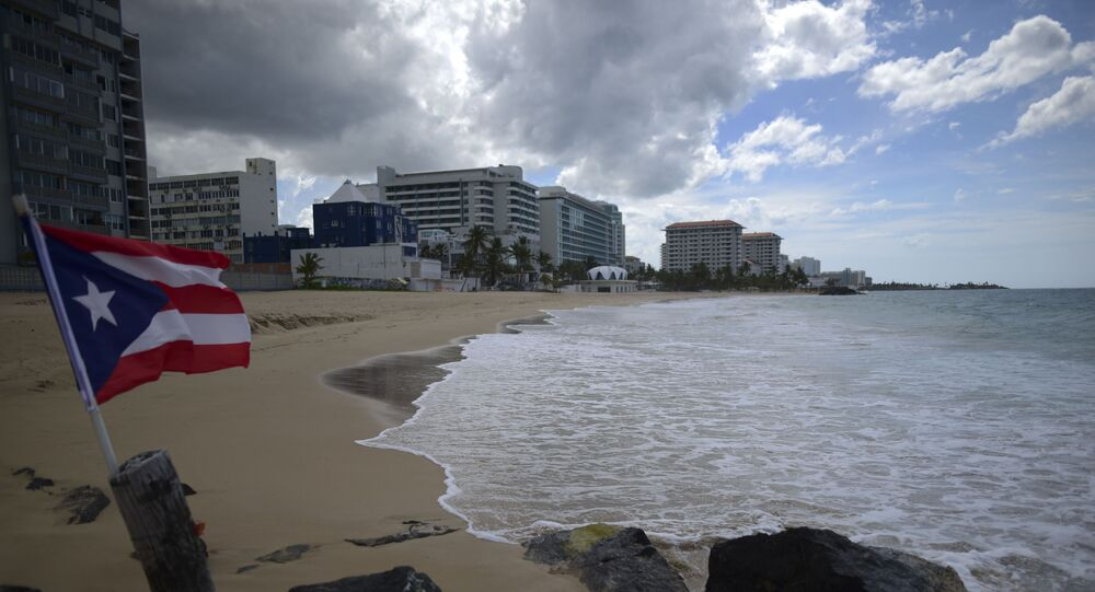 A Puerto Rican flag flies on an empty beach at Ocean Park, in San Juan, Puerto Rico, Thursday, May 21, 2020. Puerto Rico is cautiously reopening beaches, restaurants, churches, malls, and hair salons under strict conditions as the U.S. territory emerges from a two-month lockdown despite dozens of new coronavirus cases reported daily.