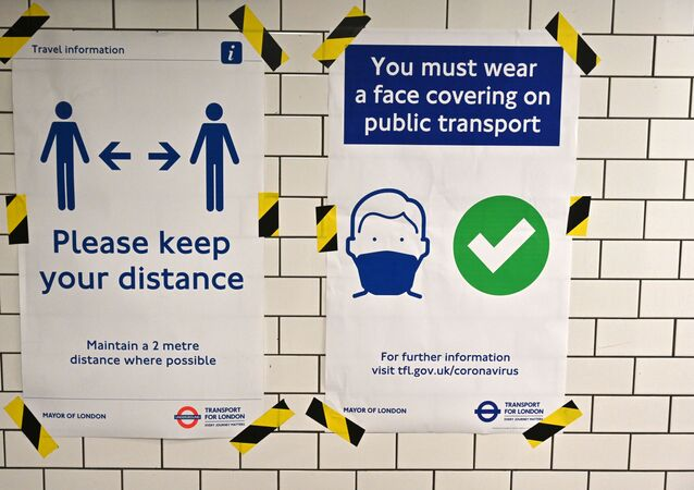 Posters advise people on social distancing and the wearing of face coverings on the underground network, at Notting Hill tube station in London, on June 15, 2020 after new rules make wearing face coverings on public transport compulsory while the UK further eases its coronavirus lockdown.