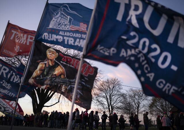 People are silhouetted as they wait to board shuttle buses to a rally for President Donald Trump, Monday, 2 November 2020.