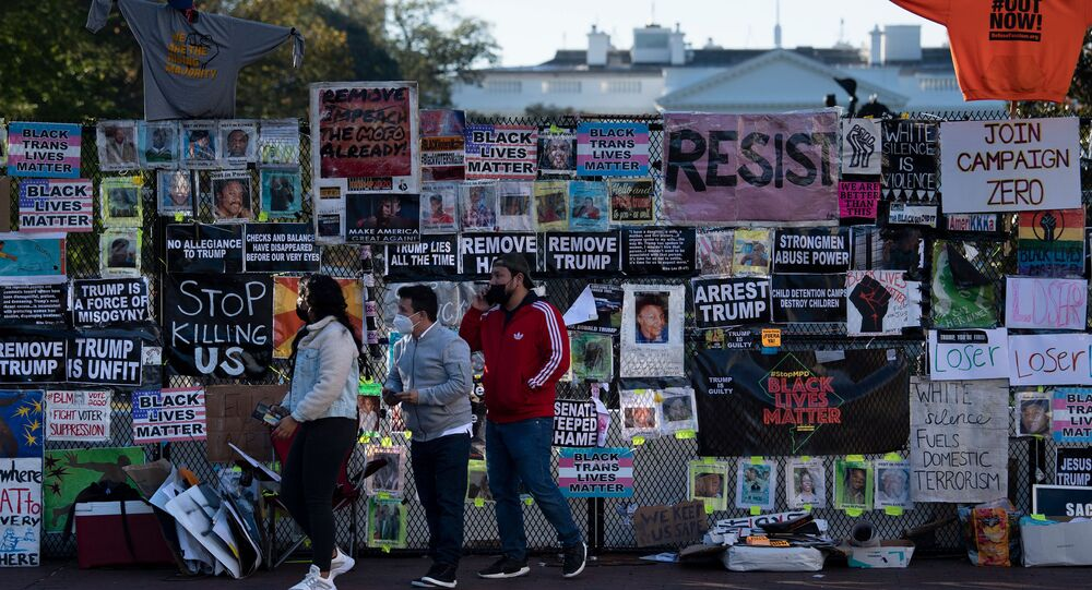 People walk past a temporary security fence around the White House covered in protest posters, as the 2020 US presidential election remains undecided on 4 November 2020, in Washington, DC.