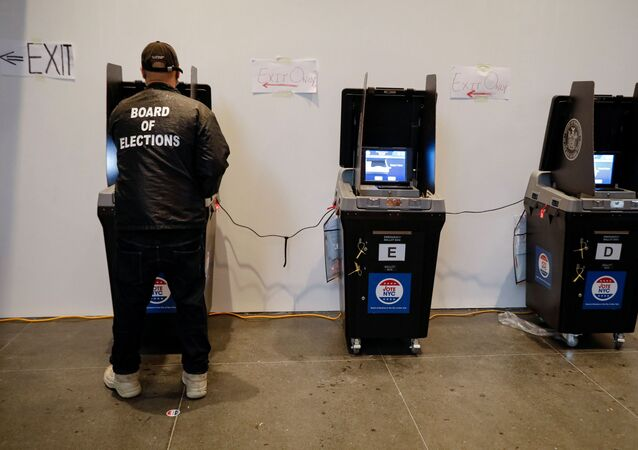 A Board of Elections employee cleans a voting machine during early voting at the Brooklyn Museum in Brooklyn, New York