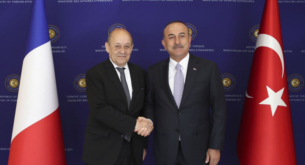 French Foreign Minister Jean-Yves Le Drian, left, and Turkey's Foreign Minister Mevlut Cavusoglu shake hands before a meeting in Ankara, Turkey, Thursday, June 13, 2019.
