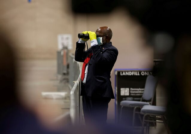 A poll watcher observes through a pair of binoculars as votes are counted at the Pennsylvania Convention Center on Election Day in Philadelphia, Pennsylvania, U.S. November 3, 2020.