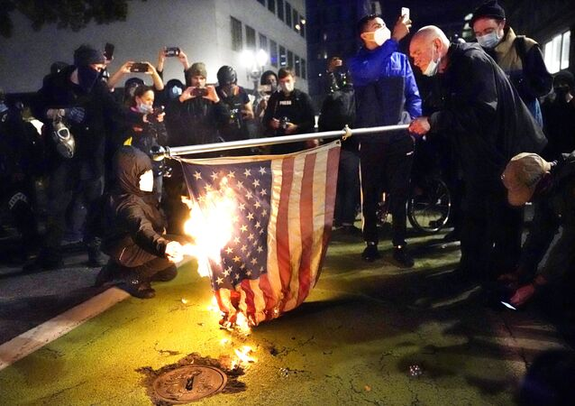 A protester lights an American flag on fire during a demonstration on 4 November 2020 in Portland, Oregon.