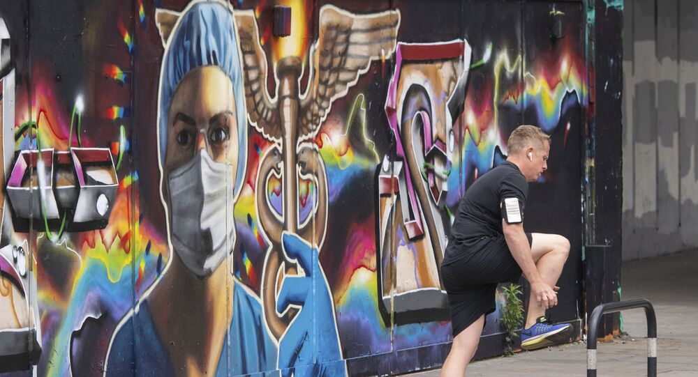 A runner pauses next to a mural showing medical images in the Shoreditch area of east London, following the introduction of measures to bring England out of the coronavirus lockdown, Thursday June 4, 2020