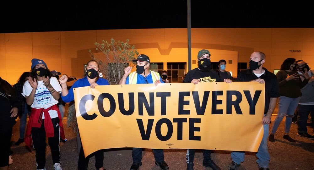 Counter-protesters, organised by Make the Road Action Nevada and PLAN Action, hold a banner during a Stop the Steal protest by supporters of US President Donald Trump at the Clark County Election Center in North Las Vegas, Nevada, US, 4 November 2020.