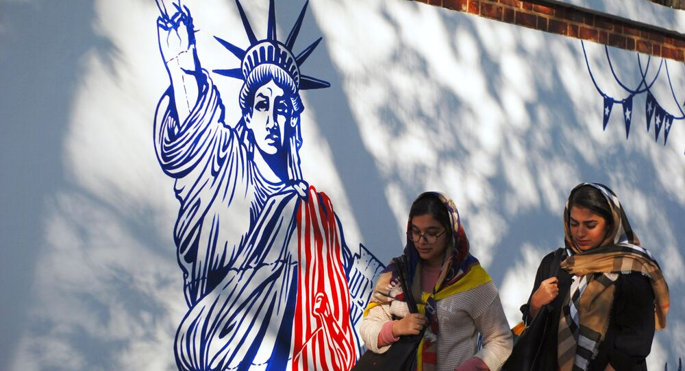 Women walk by mural on walls of former US Embassy compound in Tehran. File photo.