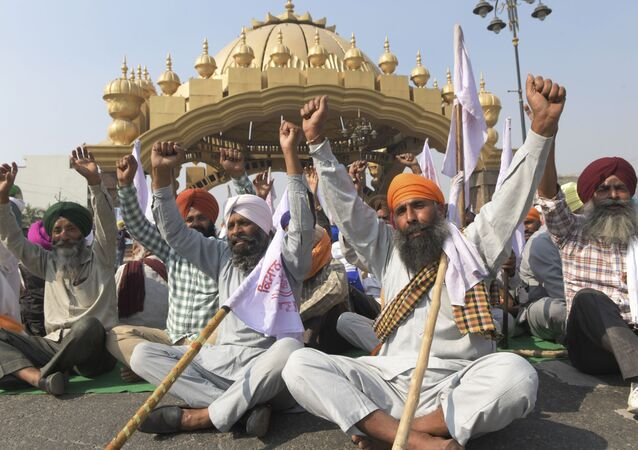 Farmers shout slogans as they block a road during a protest strike against the recent passing of agriculture reform bills in the parliament, at the golden entrance gate in Amritsar on 5 November 2020