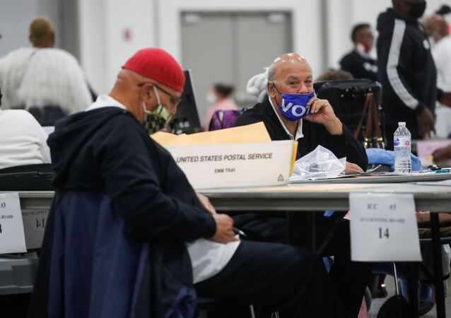A man wearing a Vote mask looks on as votes continue to be counted at the TCF Center the day after the 2020 U.S. presidential election, in Detroit, Michigan, U.S., November 4, 2020.