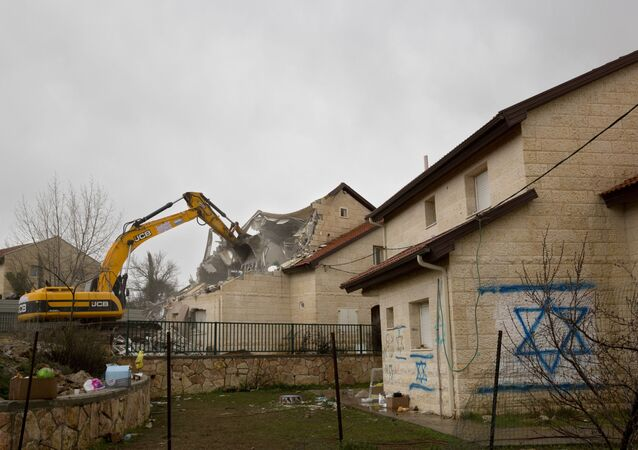 A bulldozer demolishes a house in the West Bank settlement of Ofra, Wednesday, March 1, 2017