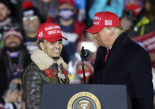 President Donald Trump brings rapper Lil Pump to the podium during a campaign event early Tuesday, Nov. 3, 2020, in Grand Rapids, Mich.
