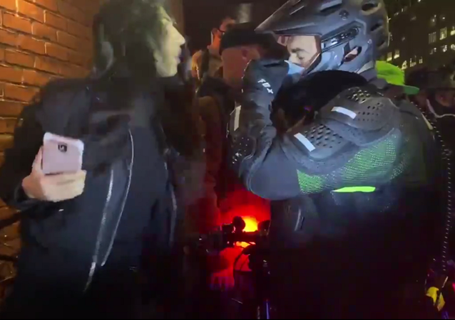 "A screenshot from a video of a woman spitting in the face of a New York City Police Department sergeant on 4 November 2020 during a ""Count Every Vote"" protest in the West Village neighborhood of the borough of Manhattan, New York City, following the US 2020 presidential election."