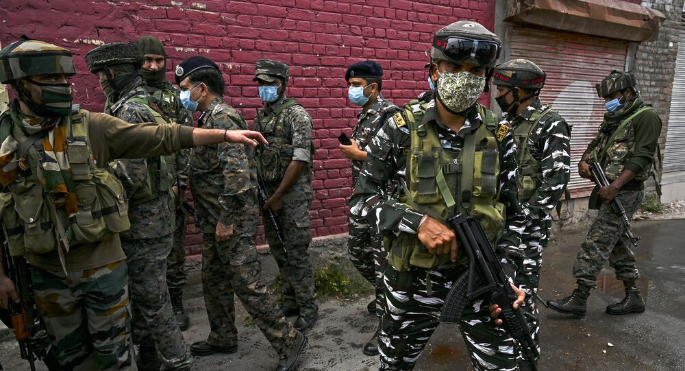 Security personnel gather near the site where suspected militants fired at police near Nowgam bypass in Srinagar on August 14, 2020. - At least two policemen were killed and another got injured after militants allegedly opened fire on police party in Nowgam area, local media reported on August 14.