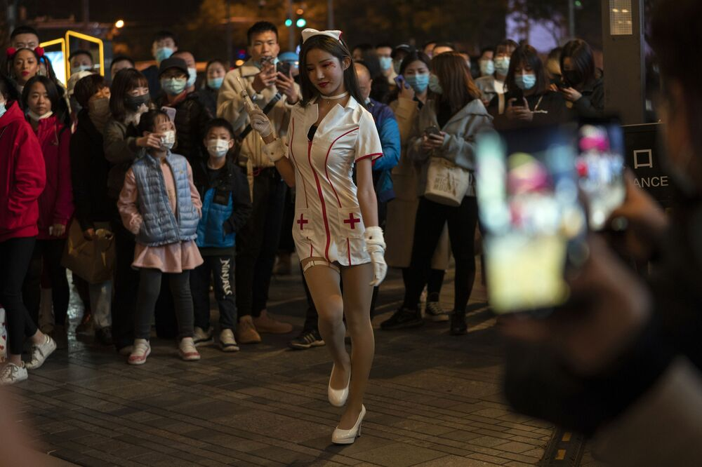 A young woman dressed as a nurse struts in a crowd gathered during Halloween night at a shopping district in Beijing on Saturday, 31 October 2020. Although Halloween is not traditionally celebrated in China, some residents in the Chinese capital took the time to dress up for a bit of fun.