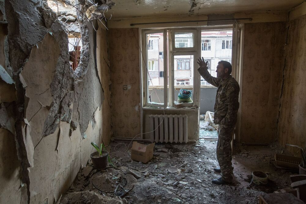 A man gestures while standing inside an apartment destroyed by shelling in Stepanakert, the capital of the unrecognised Nagorno-Karabakh republic.