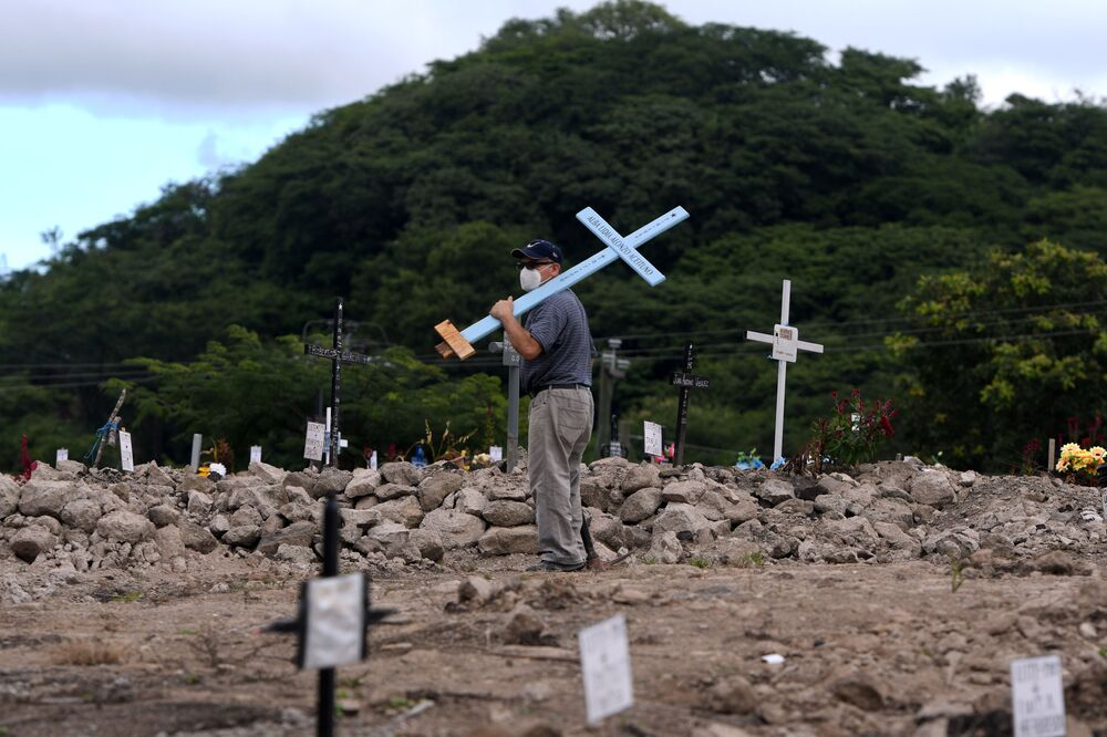 A man looks for the grave of a relative, victim of the new coronavirus pandemic, in the cemetery Covid-19, on the Day of the Dead, in Tegucigalpa, on 2 November 2020.