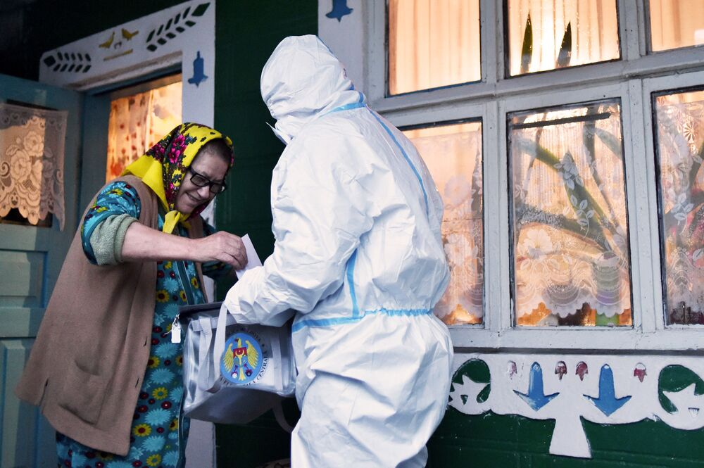 A member of a local electoral commission wearing personal protective equipment (PPE) holds a mobile ballot box as a woman casts her vote in Moldova's presidential election in the village of Stetcani, some 40 km north of Chisinau, on 1 November 2020, amid the ongoing coronavirus disease pandemic.