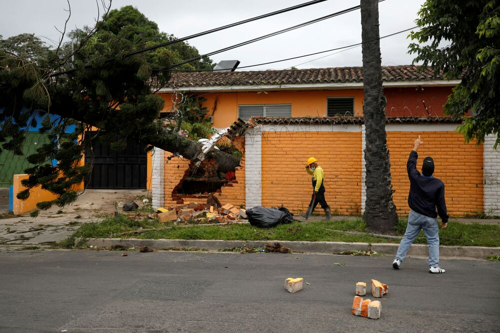 A resident points at a damaged electric power line after a tree fell from strong winds caused by tropical storm Eta in San Salvador, El Salvador, 4 November 2020.
