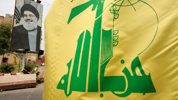 A Hezbollah flag and a poster depicting Lebanon's Hezbollah leader Sayyed Hassan Nasrallah are pictured along a street, near Sidon, Lebanon July 7, 2020.  - Sputnik International