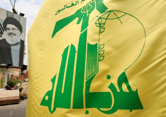 A Hezbollah flag and a poster depicting Lebanon's Hezbollah leader Sayyed Hassan Nasrallah are pictured along a street, near Sidon, Lebanon July 7, 2020.