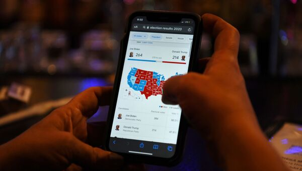 A woman uses her mobile phone to check the election results as Joe Biden's lead increases, in Houston, Texas, U.S., November 6, 2020.  - Sputnik International