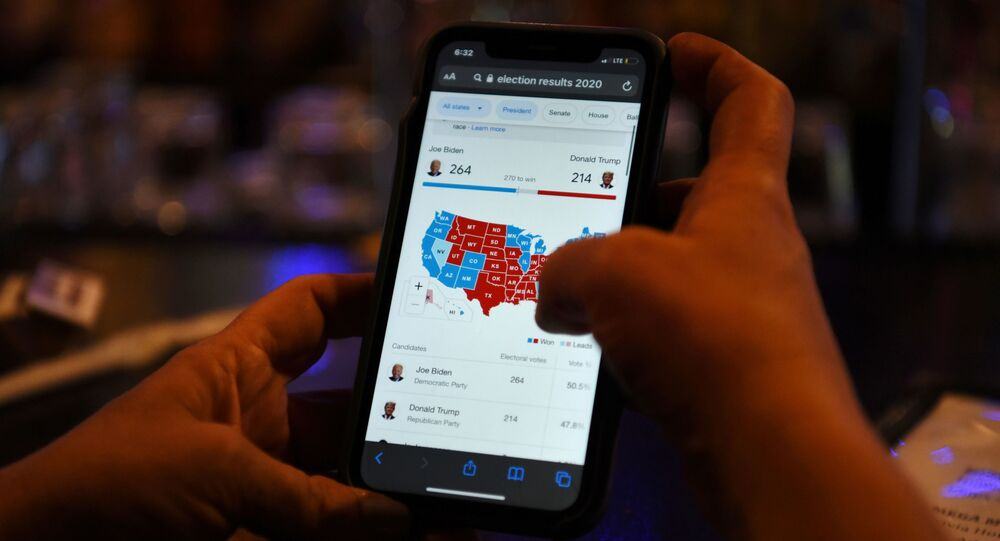 A woman uses her mobile phone to check the election results as Joe Biden's lead increases, in Houston, Texas, U.S., November 6, 2020.