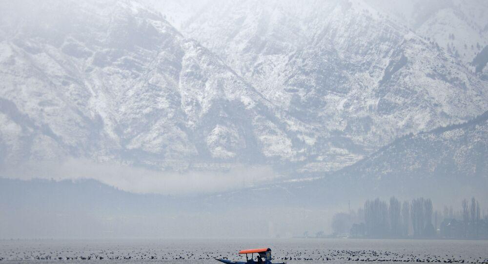 A Kashmiri boatman paddles a shikara boat during rainfall on Dal Lake in Srinagar on January 21, 2019.